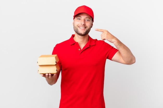 Бургер доставить человека, уверенно улыбаясь, указывая на собственную широкую улыбку