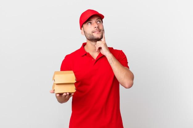 Бургер доставить человека, счастливо улыбаясь и мечтать или сомневаться