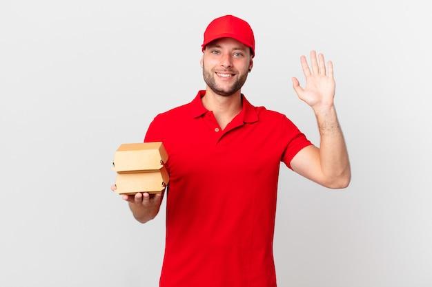 Доставка бургеров мужчина счастливо улыбается, машет рукой, приветствует и приветствует вас