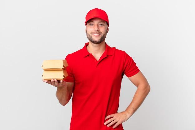 Бургер доставить мужчина счастливо улыбается, положив руку на бедро и уверенно