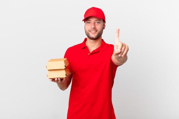 Человек доставки бургеров, гордо и уверенно улыбаясь, делает номер один