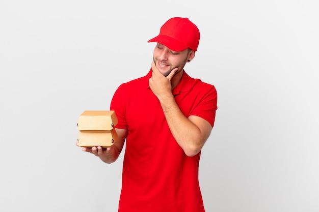 Доставка бургеров мужчина улыбается со счастливым, уверенным выражением лица, положив руку на подбородок
