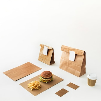 Burger; disposal cup; french fries and food parcel isolated on white backdrop