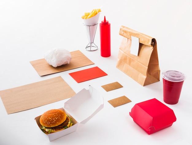 버거; 처리 컵; 소스 병; 감자 튀김과 흰색 배경에 음식 소포