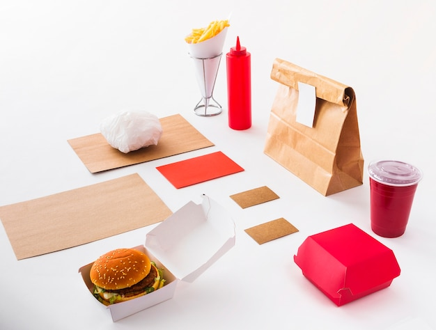 Burger; disposal cup; sauce bottle; french fries and food parcel on white background