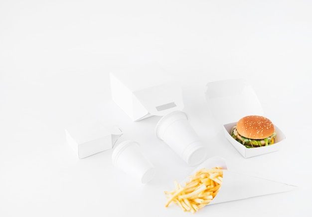 버거; 감자 튀김; 처분 컵과 음식 소포는 흰색 배경에 조롱
