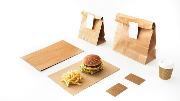 Burger and french fries on paper with disposable drink and paper package on white backdrop
