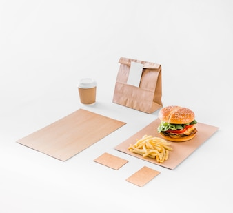 Burger; french fries; parcel and disposal cup on white backdrop
