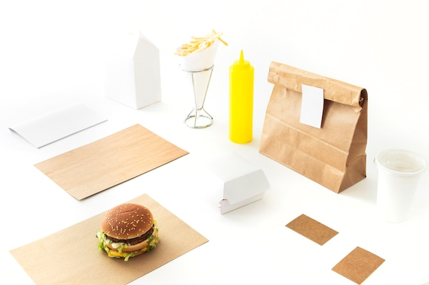 Burger; french fries; sauce and paper package on white backdrop