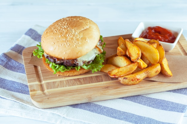 Burger and french fries on wooden surface table