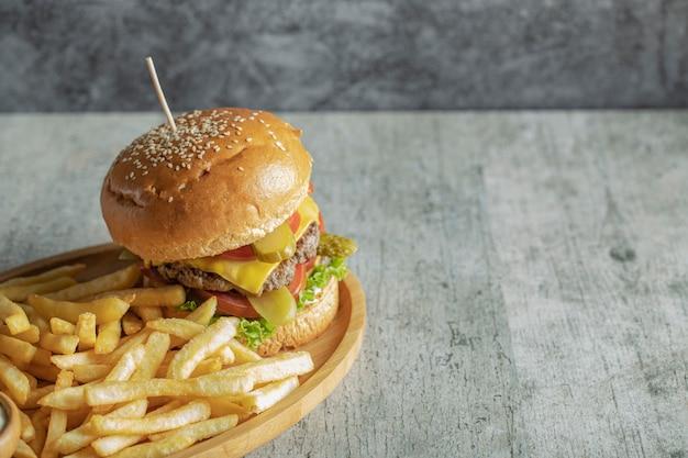 Hamburger e patate fritte in un piatto di legno