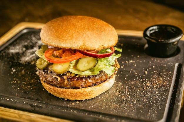 Бургер анфас с овощами, специями и картофелем фри. мясной гамбургер.