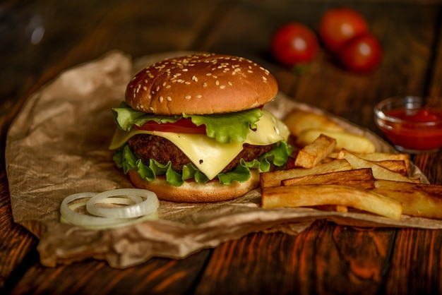 Burger or hamburger on parchment paper on a wooden table  selective focus