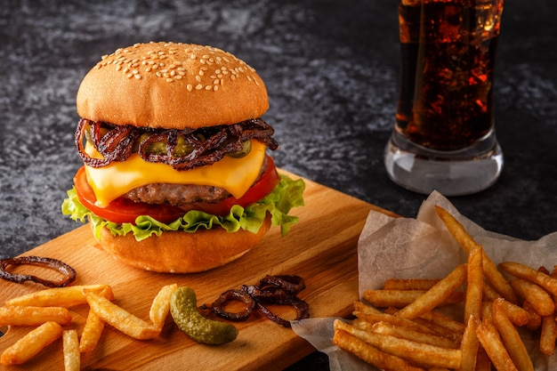 Burger, hamburger with french fries on a dark surface