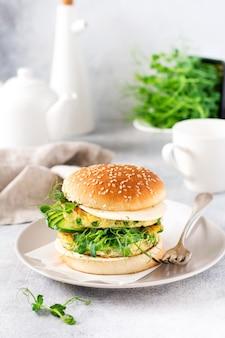 달걀과 완두콩 싹과 씨앗 마이크로그린, 신선한 샐러드, 오이 슬라이스를 밝은 배경에 있는 절단 나무 판에 얹은 건강한 채식주의자 버거. 선택적 초점
