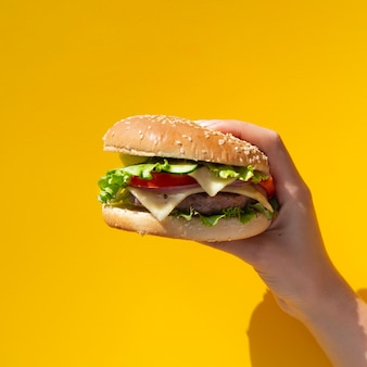 Burger held in front of yellow background