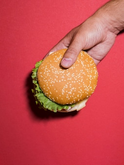 Burger held over red background