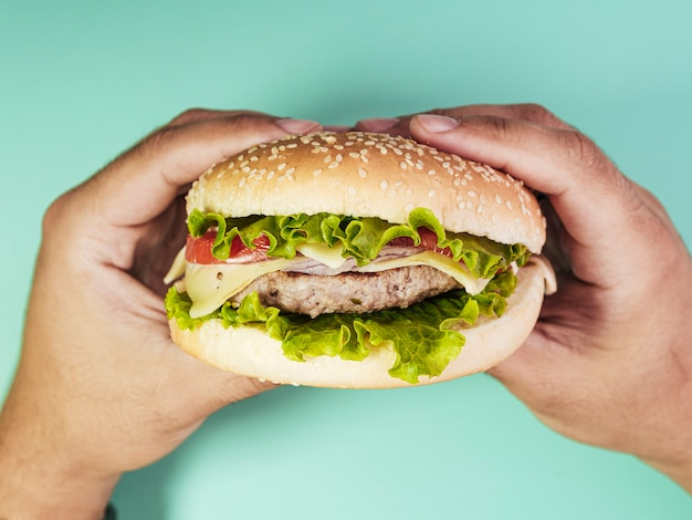 Burger held over turquoise background