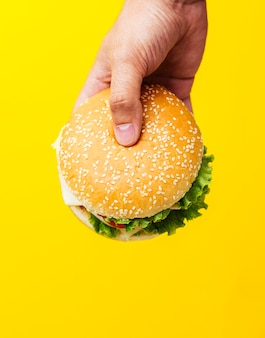Burger held over yellow background