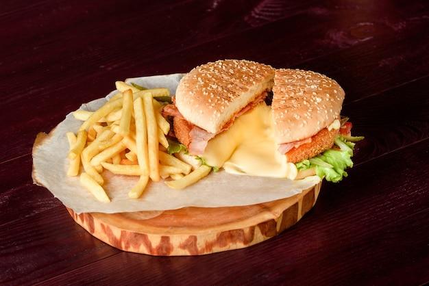 Бургер в разрезе с котлетой, плавленым сыром, беконом, листьями салата, помидорами и картофелем на пергаменте на деревянном блюде на деревянном столе.