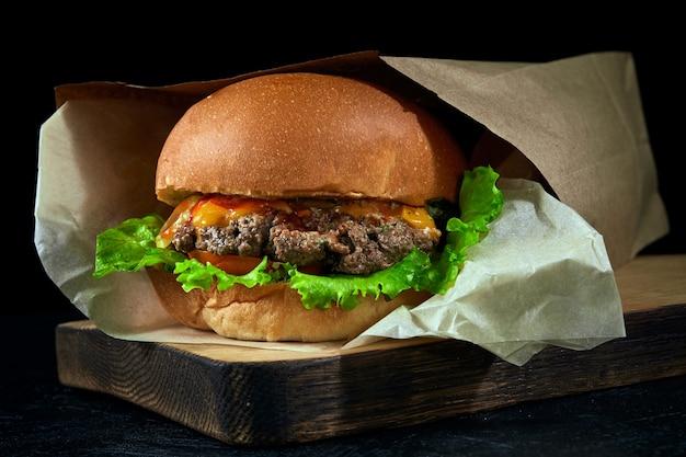 Бургер в бумажном пакете эко крафт коричневого цвета на деревянной доске и темном фоне.