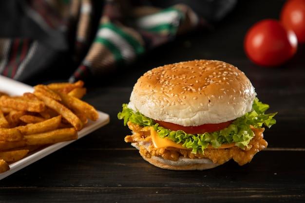 Бургер в темном деревянном столе с картофелем фри