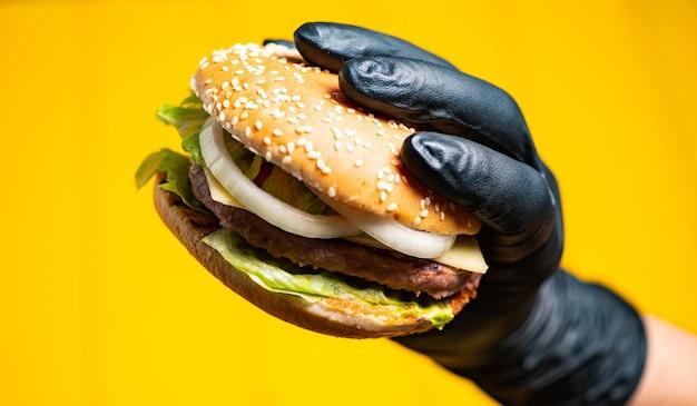 Бургер в руках в перьях на желтом