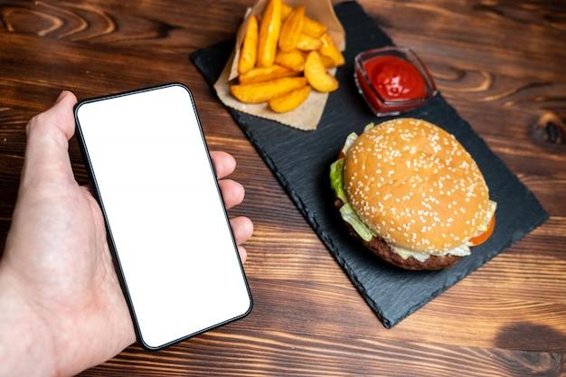 Бургер в бумаге с картофелем в деревенском и кетчупа и на шифер, черная доска и сожгли дерева фон человек держать смартфон. копировать пространство