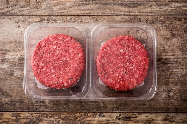 Burger meat packaged in plastic on wooden table top view
