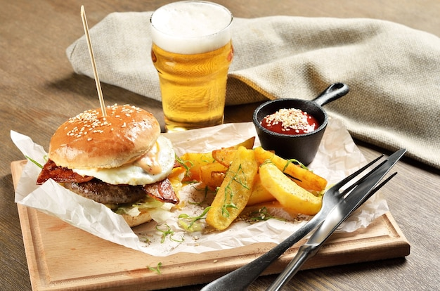 Burger, mexican potatoes and ketchup on wooden board