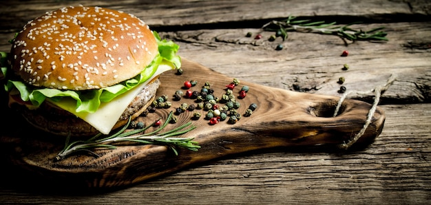 Burger on an old wooden board with spices. on wooden table.