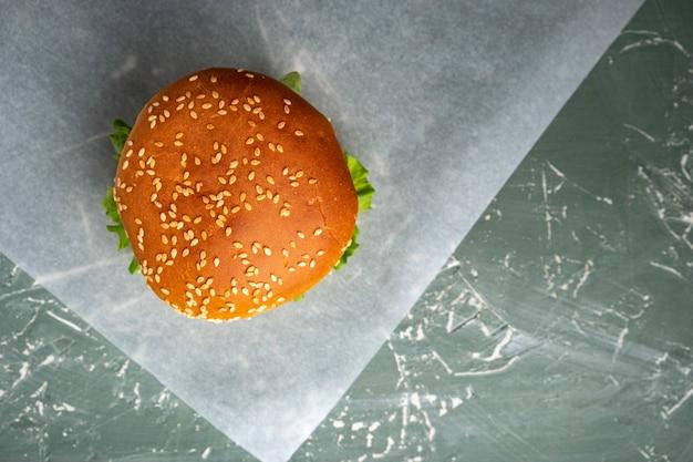 緑の背景の上面図のハンバーガー。屋台の食べ物、ファーストフード。