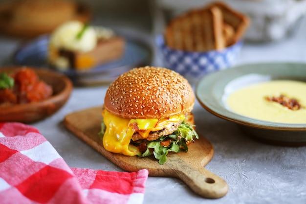 칠판에 버거 음식이 담긴 음식 테이블 치즈를 뿌린 햄버거 햄버거 패스트 푸드 테이블에 많은 음식 음식의 날 테이블에 다양한 요리 잔치 유해한 음식