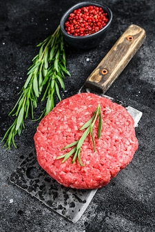 バーガーパティ、牛ひき肉。黒の背景。上面図。