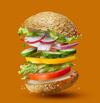 オレンジ色に分離された場所に落ちるハンバーガーの準備の材料