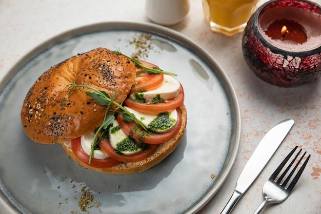 Burger sandwich with mozzarella, tomato and pesto