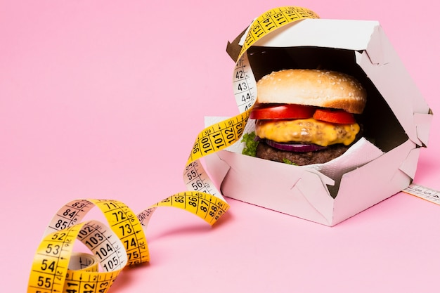 Burger in white box with tape measure