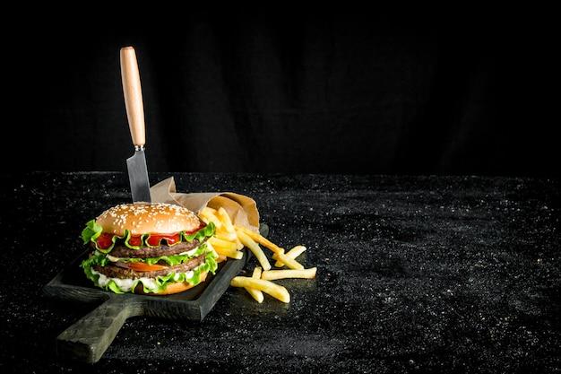 칼과 감자 튀김 버거. 소박한 배경에