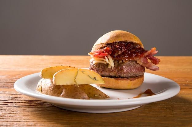 木製の背景にベーコン、チーズ、コショウとハンバーガー。