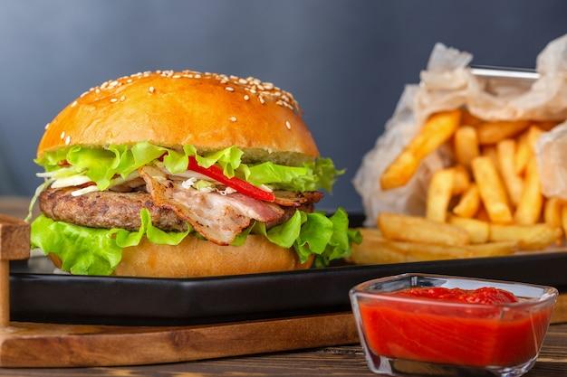 ベーコン、肉、トマト、レタスのハンバーガー、フレンチフリーの木製モダンプレート。
