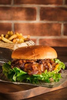 木の板に牛肉とキャラメリゼした玉ねぎを添えたハンバーガー。タマネギと牛肉のチーズバーガー。ジューシーで美味しい自家製バーガー。