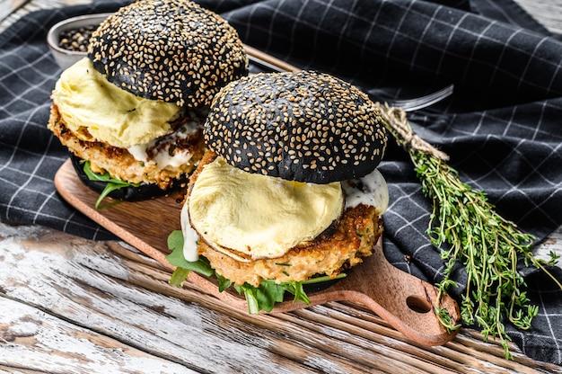 Burger with a black bun brioche, scrambled eggs, beef patty and arugula. white background. top view.