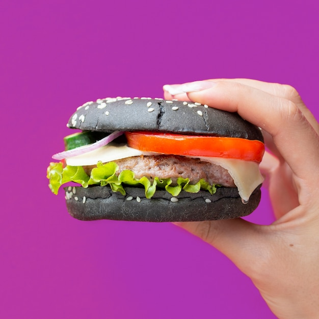Burger with black bun on purple background