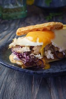 Бургер с сыром и беконом на круглой тарелке