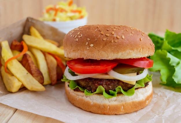 Бургер с сыром, помидорами и сочными котлетами. салат из капусты. жареный картофель.