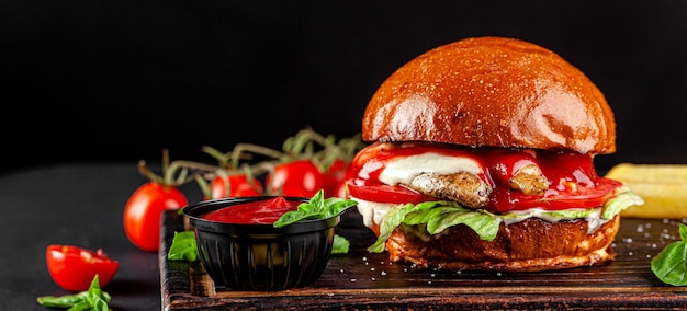 Burger with chicken, cheese, tomatoes, lettuce, and tomato sauce
