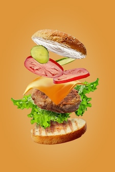 Burger with flying ingredients isolated