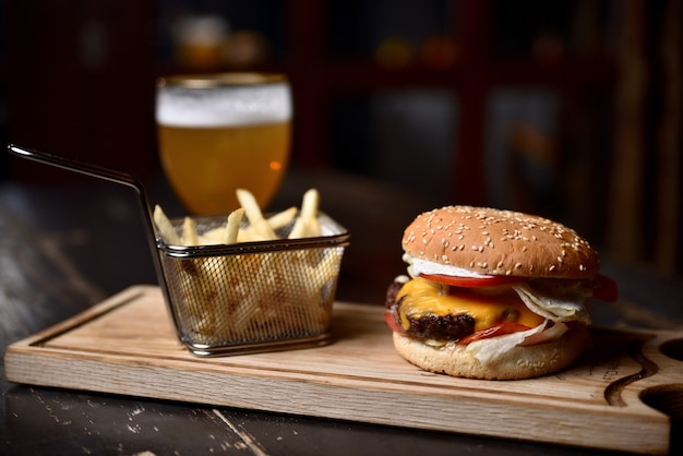 Burger with french fries and beer on a wooden board