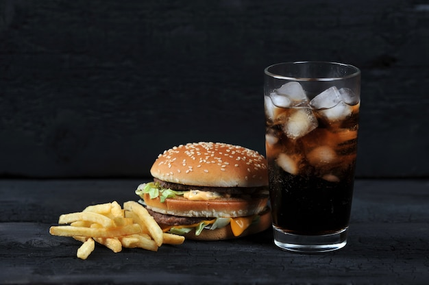Burger with french fries and a glass with ice cola