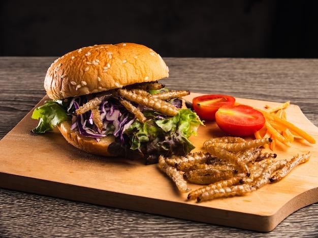 Бургер с жареной бамбуковой гусеницей и овощным салатом на деревянной тарелке.